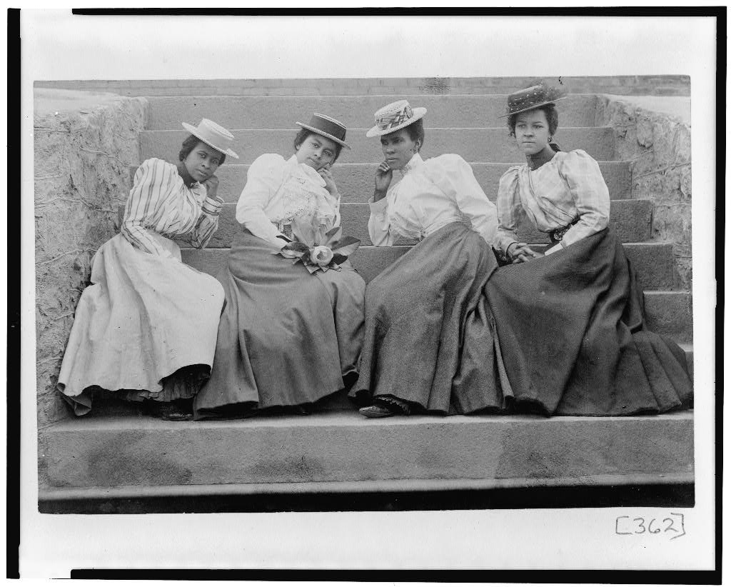Four African American women seated on steps of building at Atlanta University, Georgia, photographer Askew, Thomas E.