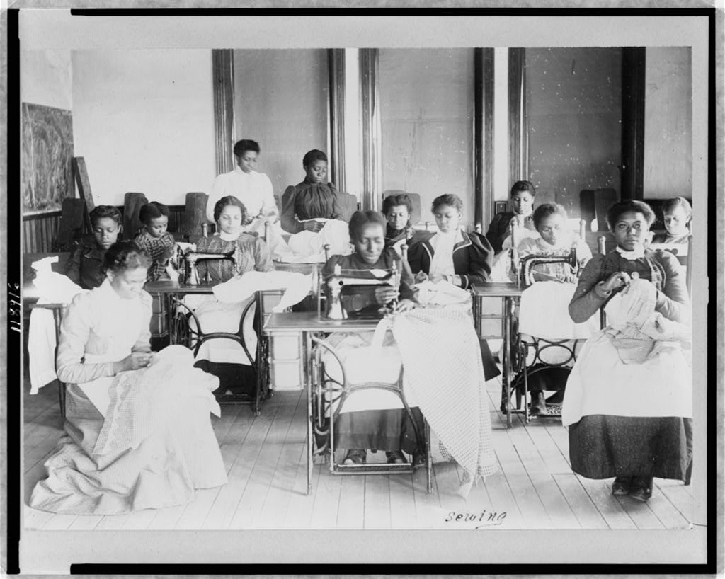 Young women sewing with machines and by hand in the sewing class at the Agricultural and Mechanical College, Greensboro, N.C, Library of Congress.