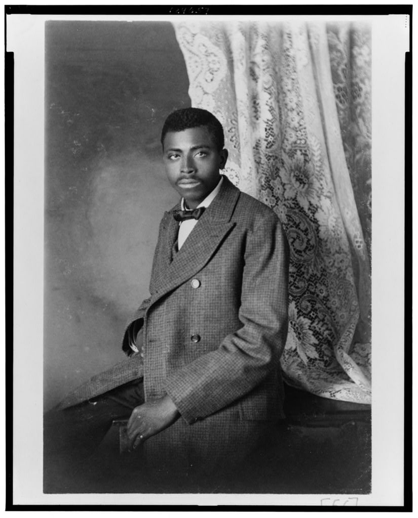 African American man, three-quarter length portrait, seated, facing left