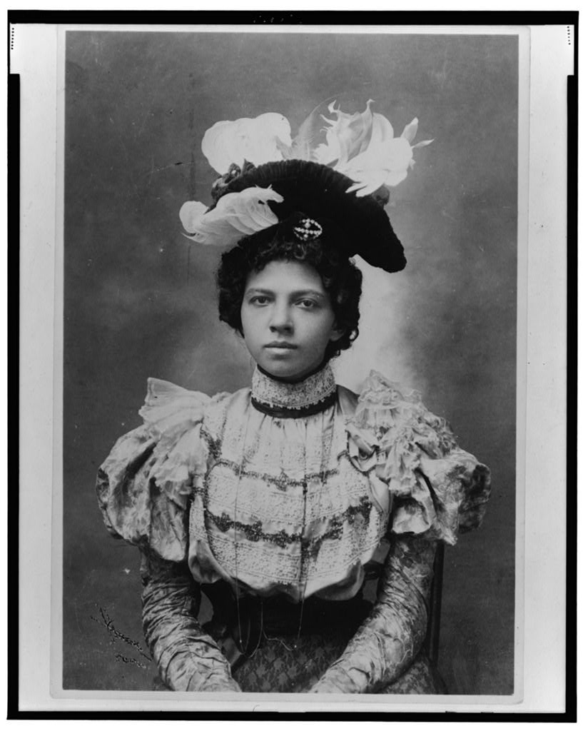 African American woman, half-length portrait, wearing hat, facing front