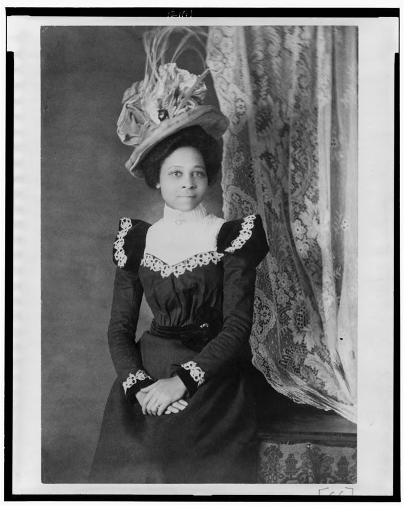 Young African American woman, three-quarter length portrait, facing slightly right, with hands folded on her lap, Attribution to Askew from Photography on the color line
