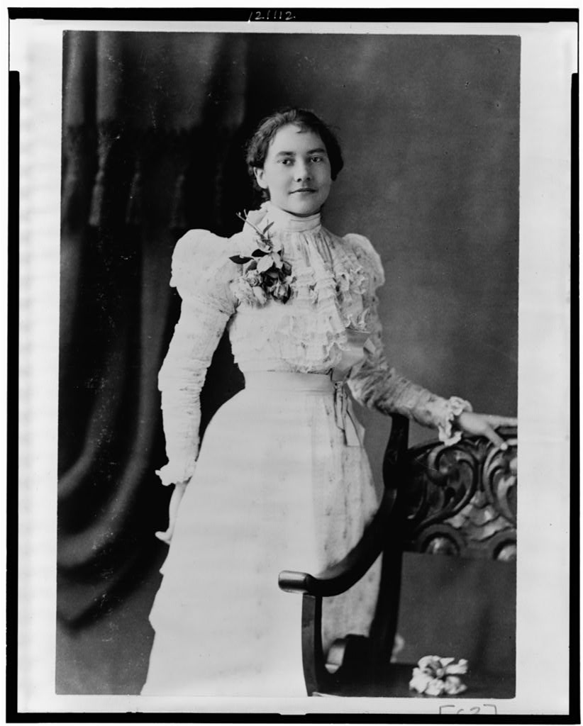 Young African American woman, three-quarter length portrait, standing, facing slightly right, with left hand on back of chair